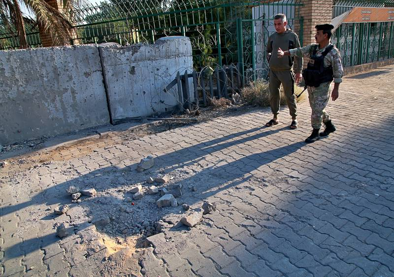 Security forces inspect the scene of the rocket attack at the gate of al-Zawra public park in Baghdad, Iraq, Nov. 18, 2020.