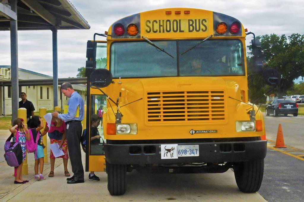 William Woodland, Randolph elementary school associate principle, ensures the children get on the right bus Aug. 27, 2013, in front of the elementary school at Joint Base San Antonio-Randolph in Texas.