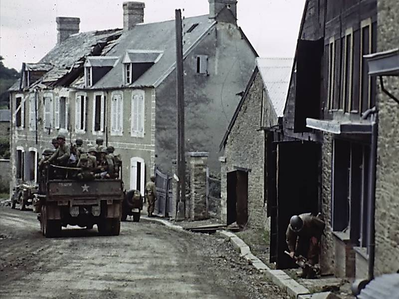 U.S. troops drive through a town during World War II in France