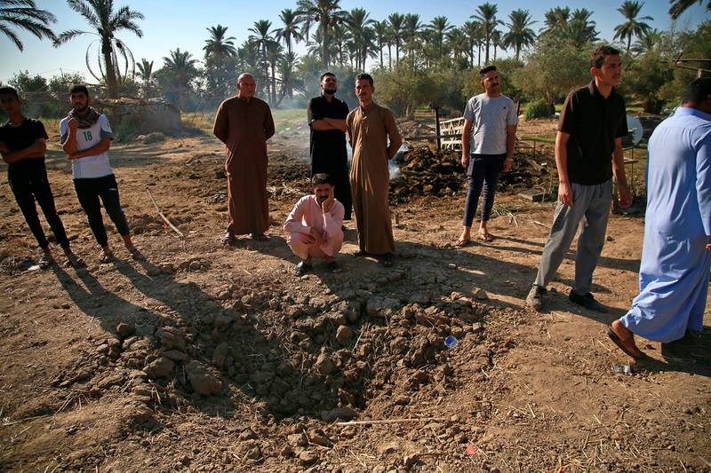 People inspect a crater caused by a deadly Katyusha rocket attack near international airport in Baghdad, Iraq, Tuesday, Sept. 29, 2020.