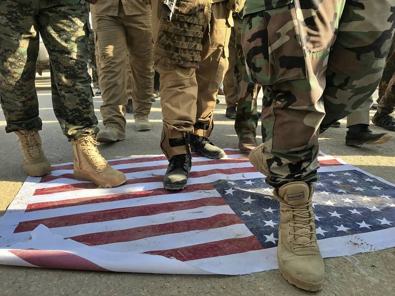 Mourners step over the print of a U.S. flag during the funeral procession of Abu Ali al-Dabi, a fighter of the Popular Mobilization Forces, during his funeral procession in Baghdad, Iraq, Monday, Aug. 26, 2019.