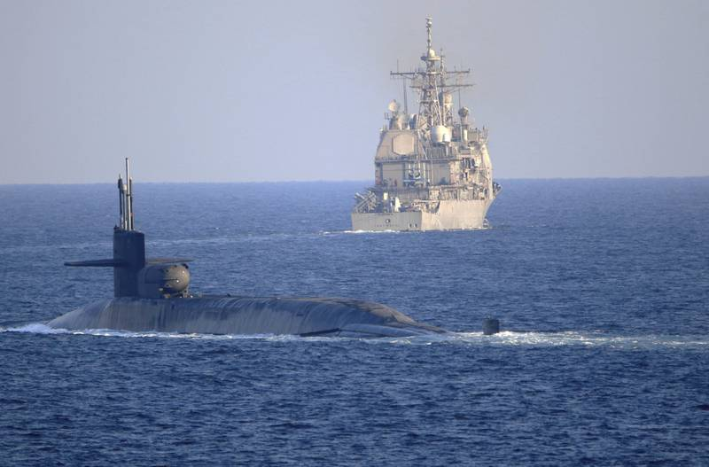 The guided-missile submarine USS Georgia, front, with the guided-missile cruiser USS Port Royal, transits the Strait of Hormuz in the Persian Gulf on Dec. 21, 2020.