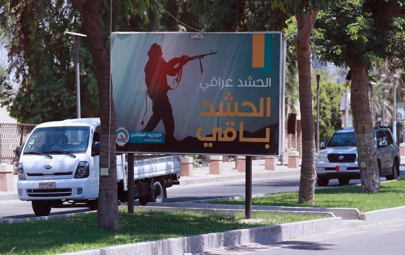 Motorists pass by a Popular Mobilization poster in Baghdad, Iraq, on June 26, 2020. Iraqi security forces arrested over a dozen men suspected of a spate of rocket attacks against the U.S.
