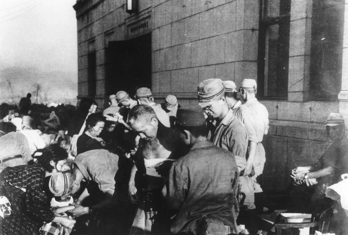 In this Aug. 6, 1945, file photo, survivors are seen as they receive emergency treatment by military medics shortly after the first atomic bomb ever used in warfare was dropped by the United States over Hiroshima, Japan.