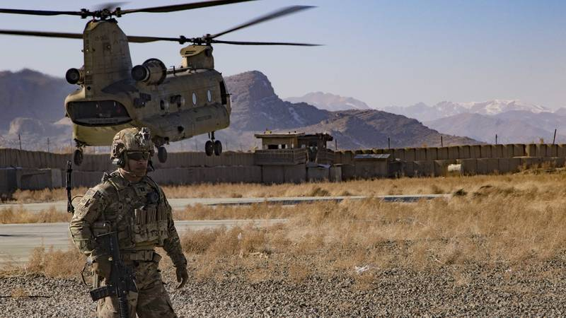 U.S. Army Capt. Bradley D. Rager, assigned to the Headquarters and Headquarters Battalion, 1st Armored Division, helps secure the helicopter landing zone as a CH-47 Chinook helicopter prepares to land at an Afghan military base Dec. 14, 2019, in southeastern Afghanistan.