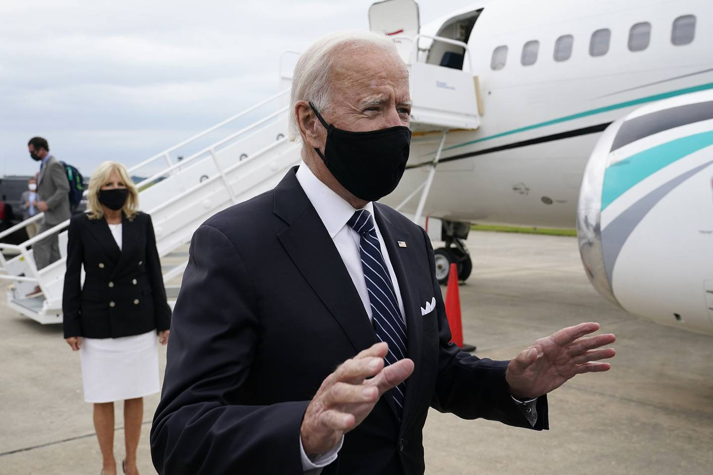 Democratic presidential candidate and former Vice President Joe Biden speaks with reporters after he and his wife Jill Biden, back left, stepped off a plane at New Castle Airport in New Castle, Del., Friday, Sept. 11, 2020.