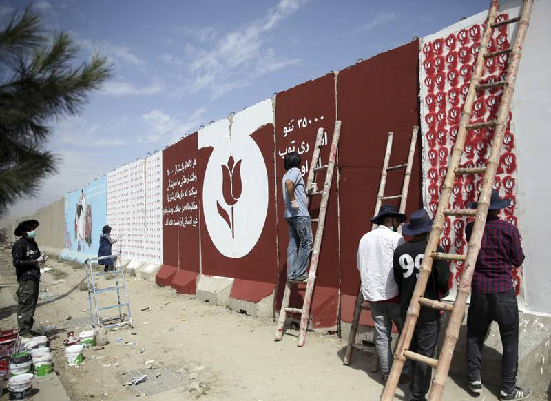 In this Friday, Aug. 30, 2019 photo, independent Afghan artists paints tulips on blast walls in Kabul, Afghanistan.