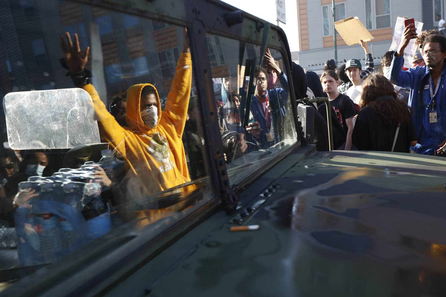 Protesters stand near a Minnesota National Guard vehicle Friday, May 29, 2020, in Minneapolis. Protests continued following the death of George Floyd, who died after being restrained by Minneapolis police officers on Memorial Day.