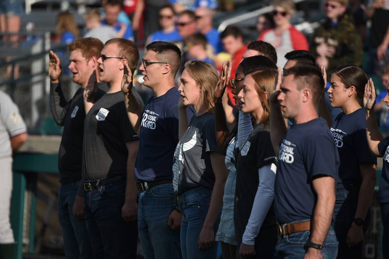 Recent enlistees in various branches of the U.S. military recite the oath of enlistment during a commitment ceremony at the Military Appreciation Night for the Fargo-Moorhead RedHawks baseball game on June 18, 2019, at Newman Outdoor Field, Fargo, N.D.