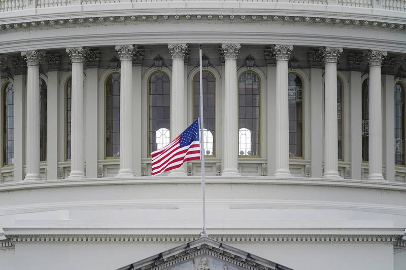 An American flag flies at half-staff in remembrance of U.S. Capitol Police Officer Brian Sicknick above the Capitol Building in Washington, Friday, Jan. 8, 2021.