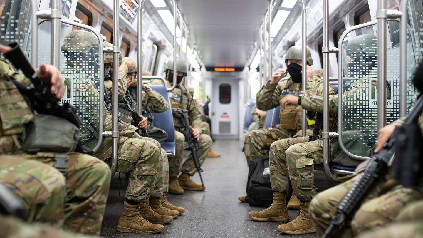 Soldiers with the North Carolina National Guard ride a Metro train that will get them to the station they will guard for the 59th Presidential Inauguration in Washington on Jan. 20, 2021.
