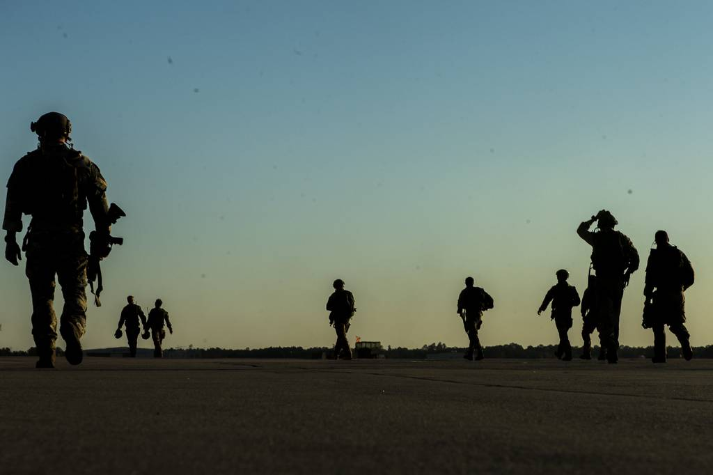U.S. soldiers with the 20th Special Forces Group walk on a flight line in Gulfport, Miss., May 5, 2014, during Emerald Warrior 2014, a U.S. Special Operations Command-sponsored exercise designed to provide realistic military training in an urban setting.