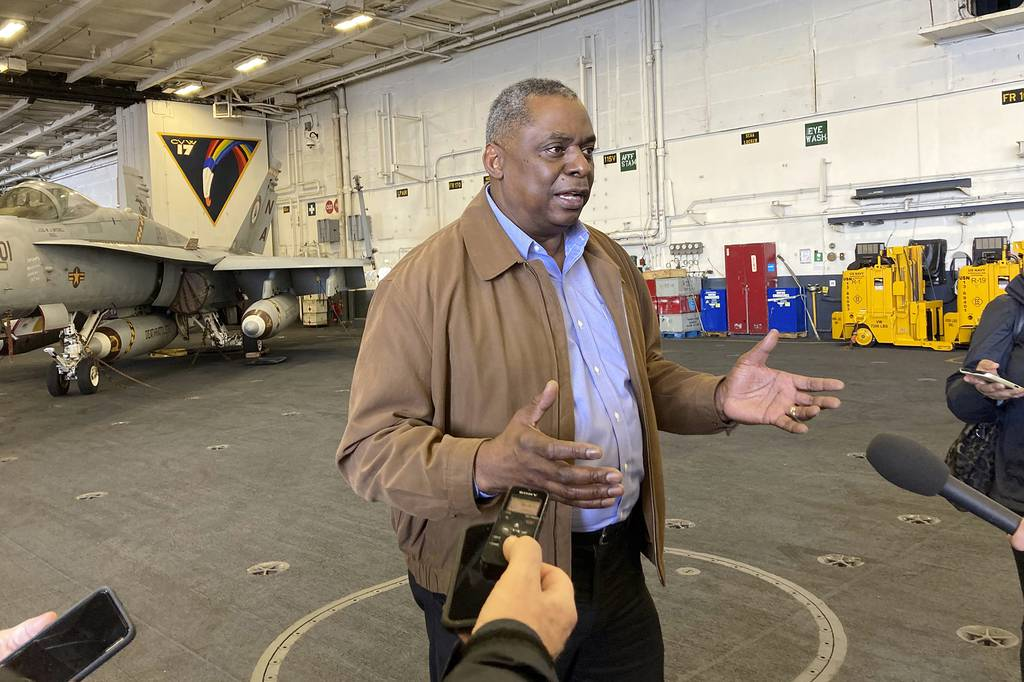 Defense Secretary Lloyd Austin speaks to reporters after arriving on the aircraft carrier USS Nimitz, Thursday, Feb. 25, 2021, at sea.