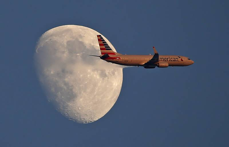 An American Airlines jetliner flies past the moon on Sept. 1, 2017, in Arlington, Texas.