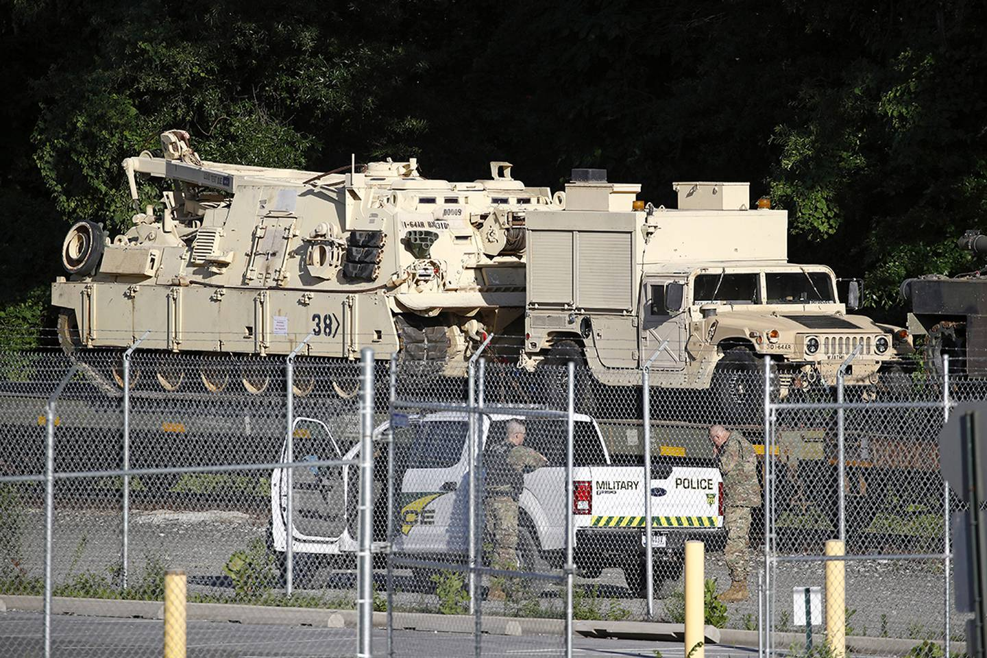 Military police stand military vehicles on a flat car in a rail yard, Monday, July 1, 2019, in Washington, ahead of a Fourth of July celebration that President Donald Trump says will include military hardware.