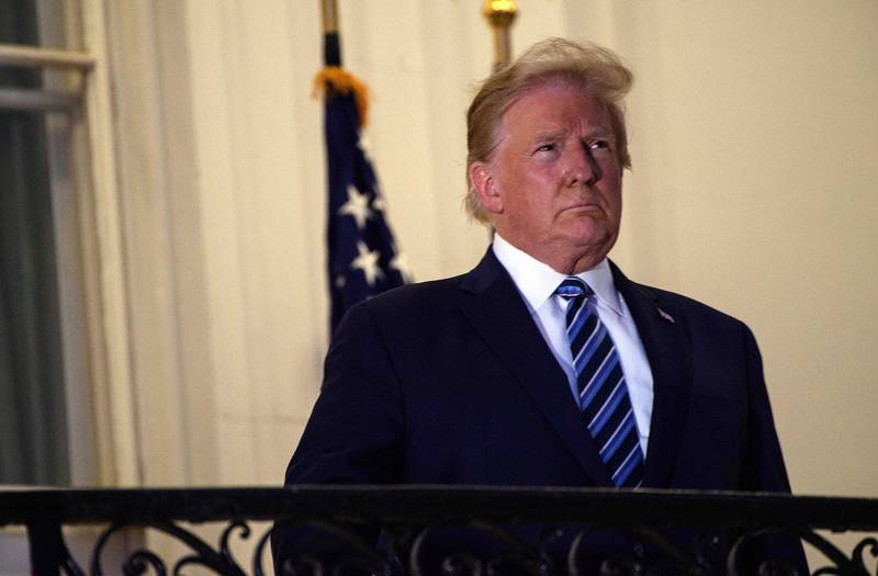 President Donald Trump looks out from the Truman Balcony upon his return to the White House from Walter Reed Medical Center, where he underwent treatment for COVID-19, in Washington on Oct. 5, 2020.