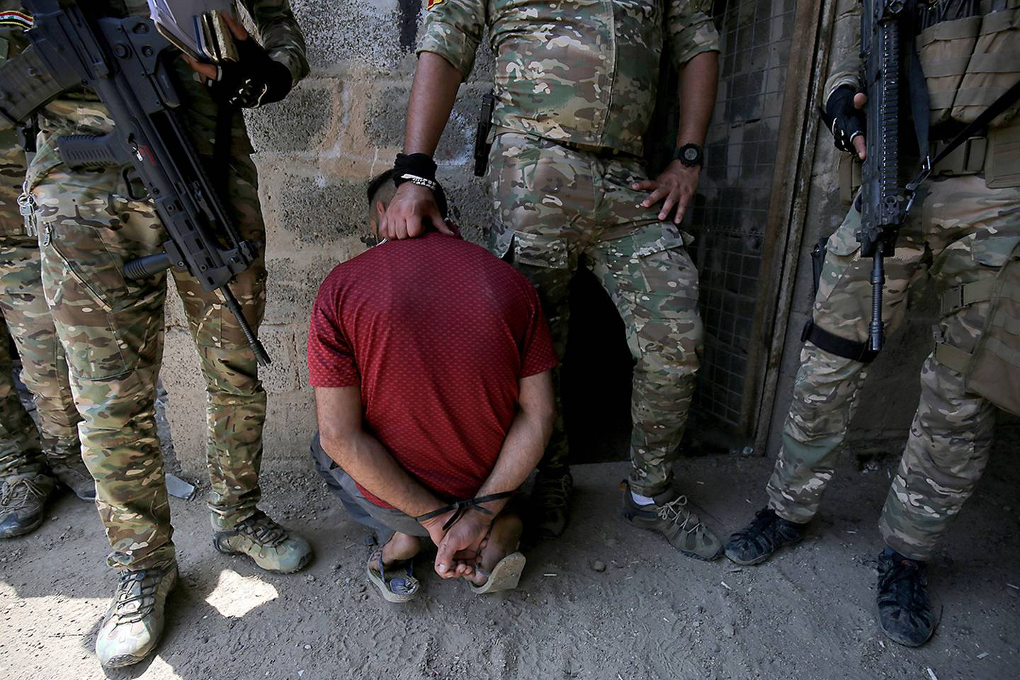 Iraqs rapid response forces detain a man as they storm a house in the Tarmiyah district, north of Baghdad, searching for wanted Islamic State group suspects on July 21, 2019.