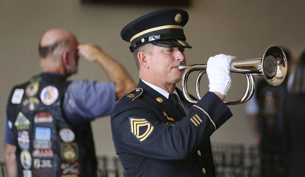 """A member of the U.S. Army Honor Guard plays """"Taps"""" in memory of Stephen Jerald Spicer, a homeless U.S. Army veteran, during a full military honors service at Woodlawn Memorial Park in Gotha, Fla., July 18, 2019."""
