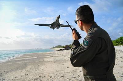 """Capt. Orr """"Recoil"""" Genish, 37th Bomb Squadron weapons systems officer, uses a land mobile radio as he watches a B-1B Lancer land in support of a Bomber Task Force mission at Naval Support Facility Diego Garcia, Oct. 17, 2021. (Staff Sgt. Hannah Malone/Air Force)"""