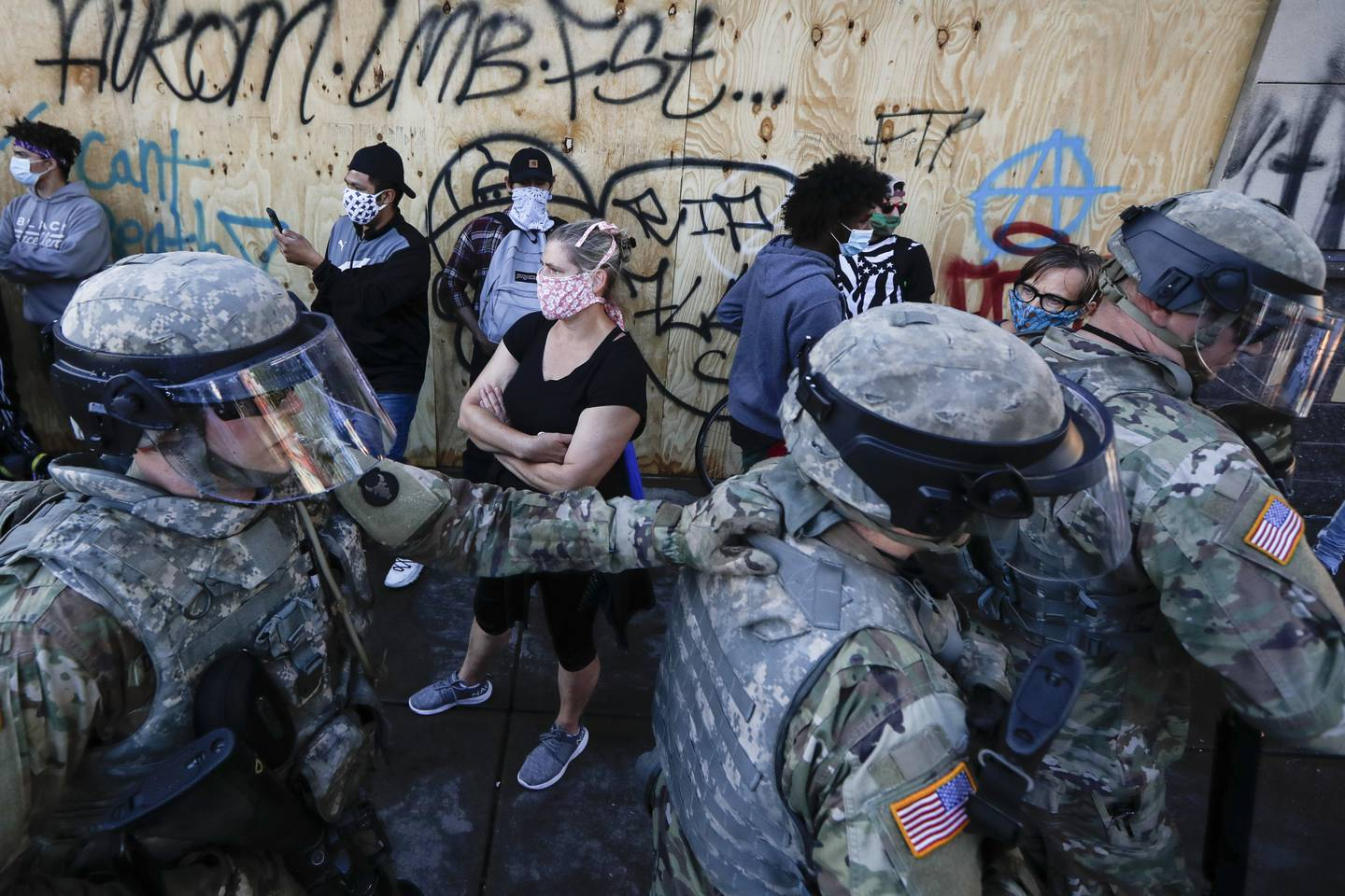 National Guard personnel return to their defensive position as protesters make room for them to fall back following a confrontation on East Lake Street, Friday, May 29, 2020, in St. Paul, Minn.
