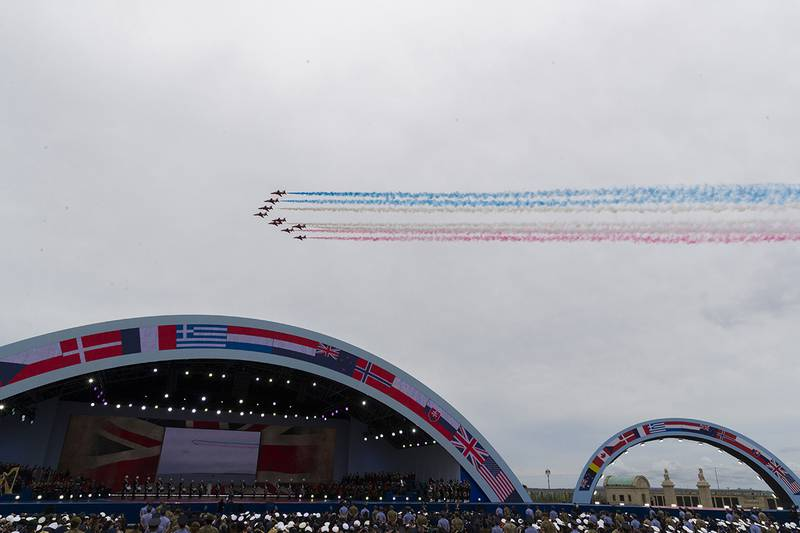A flyover trails colored smoke to conclude a ceremony to mark the 75th Anniversary of D-Day