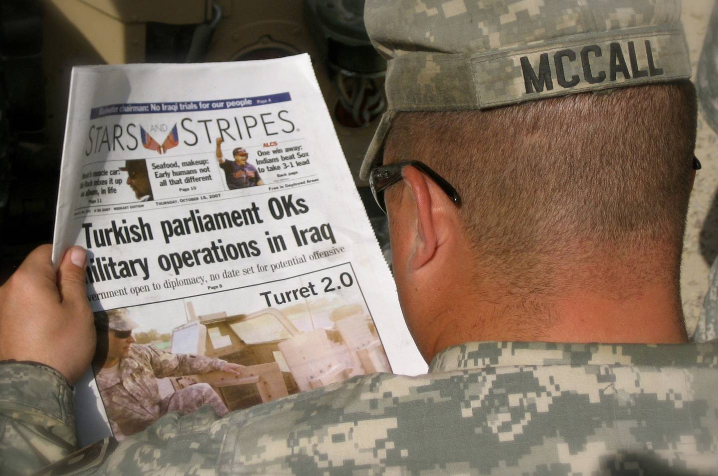 An Army MP reads an edition of the Stars and Stripes newspaper while in the Green Zone, Baghdad, Oct. 18, 2007.