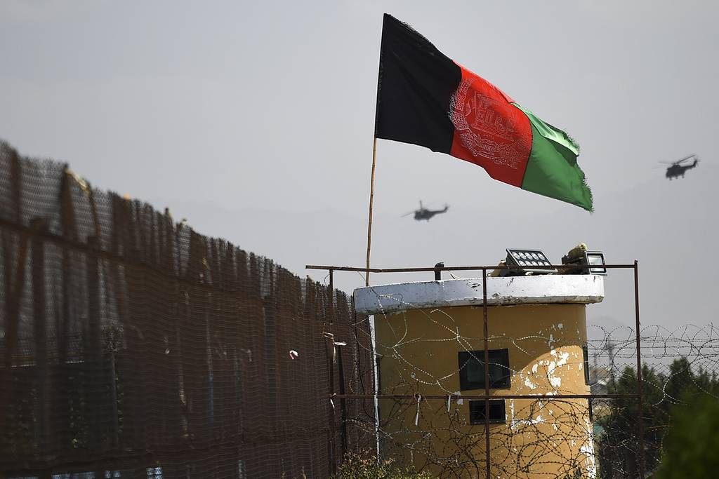 Two U.S. military helicopters are seen flying past an Afghan national flag during the 100th anniversary of the country's Independence Day in Kabul on Aug. 19, 2019.