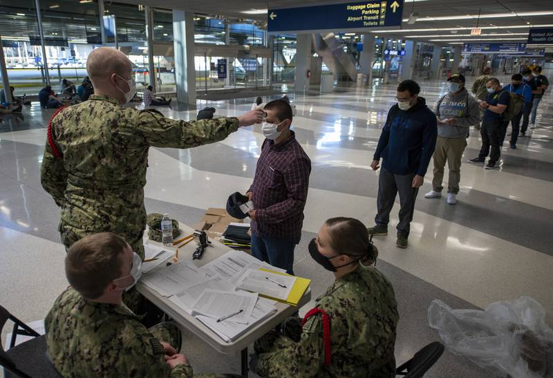 Staff assigned to Recruit Training Command process recruits on April 21, 2020, as part of a preliminary health screening at Chicago O'Hare International Airport.