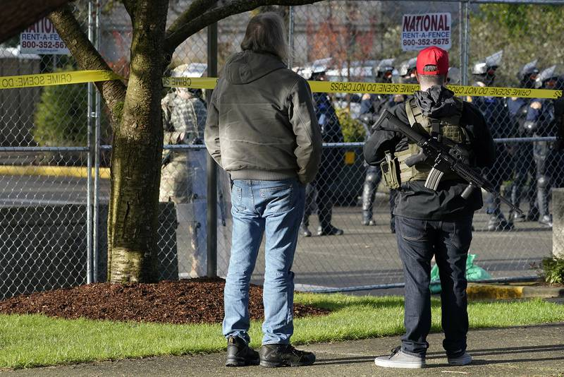 An armed supporter of President Donald Trump looks in at a gathering of Washington State Patrol troopers behind a perimeter fence during a rally, Sunday, Jan. 10, 2021, at the Capitol in Olympia, Wash.