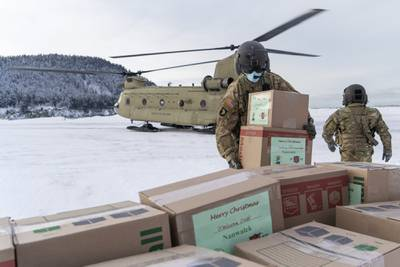 Soldiers unload gifts from a CH-47 Chinook helicopter in Nanwalek, Alaska, during Operation Santa Claus, on Dec. 11, 2020.
